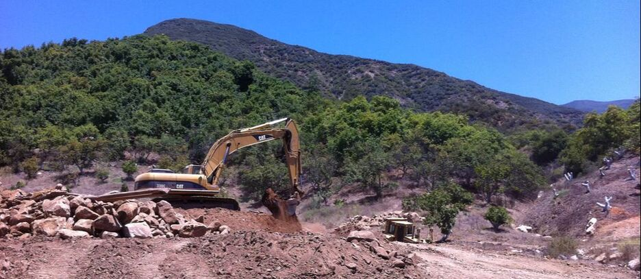 Excavator digging on gentle slope, with a hill in the background.